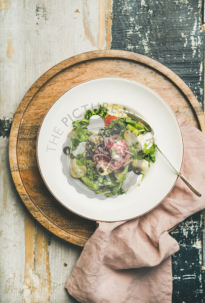 Fresh green summer salad with artichokes over wooden background