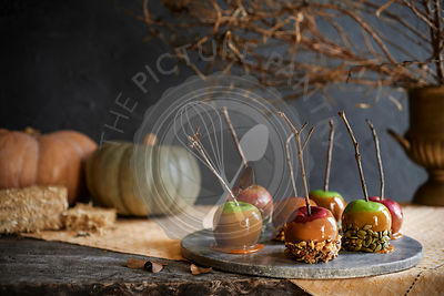 Marble tray of caramel apples with fall decor in the background. Moody and fall themed.