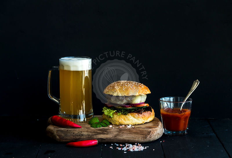 Fresh homemade burger on wooden serving board with spicy tomato sauce, sea salt, herbs and mug of light beer over black background.
