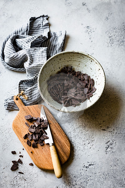 Chopped chocolate in a ceramic bowl, alongside a chopping board with knife
