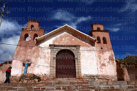 Woman and donkey walking past old adobe colonial church, Maras, Cusco Region, Peru
