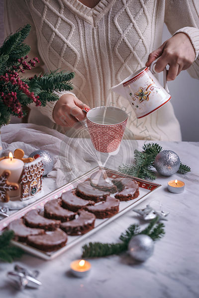 Woman eating Christmas chocolate crescent cookies and drinking milk