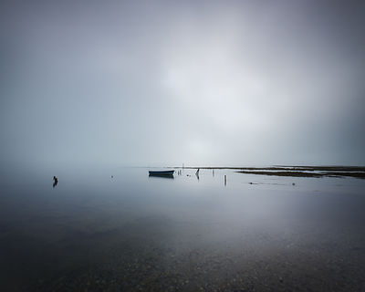 Theatrical lighting on a calm sea, as the sun struggles to break through heavy fog on the Solent, near Lymington, Hampshire, UK