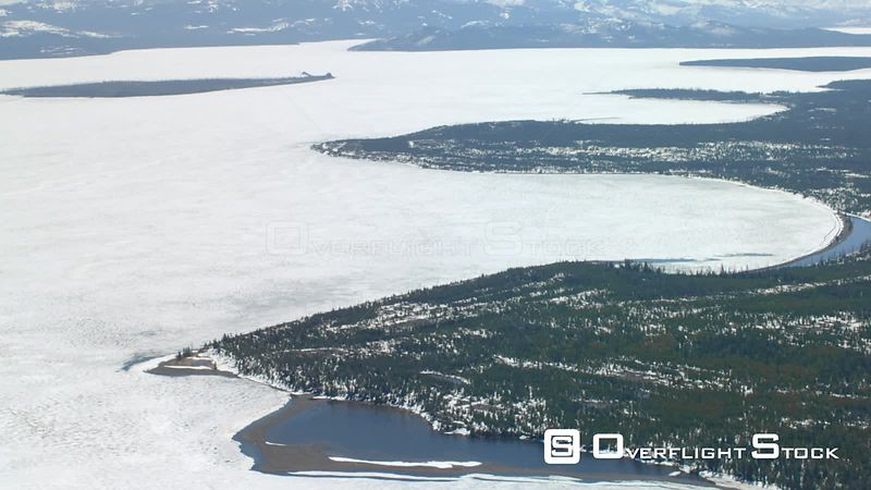 Ice covered Yellowstone lake sits in the heart of Yellowstone National Park, with the Absaroka mountain range in the background