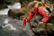Backpacker taking water from stream