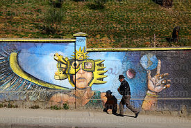 Man walking past mural showing the Sun God Inti and Tiwanaku symbols, La Paz, Bolivia