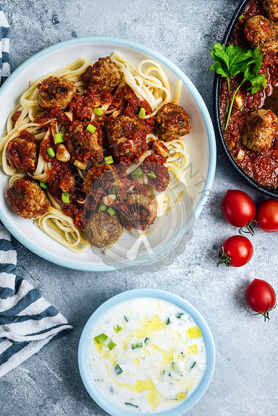 Meatballs with tomato sauce served on pasta photographed from top view. Yogurt and cucumber dip in a small bowl and tomatoes accompany.