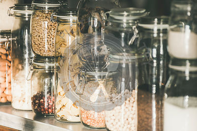 Grains, cereals, nuts, dry fruit, pasta in jars, selective focus
