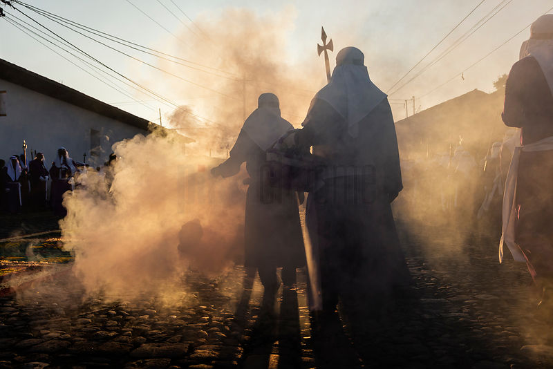Penitants Walking with Incense Burners at Sunrise During a Good Friday Parade
