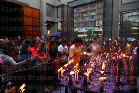 Devotees offering candles to Señor de los Milagros in courtyard behind Las Nazarenas church, Lima, Peru