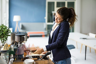 Smiling businesswoman on the phone preparing espresso with espresso machine in a loft