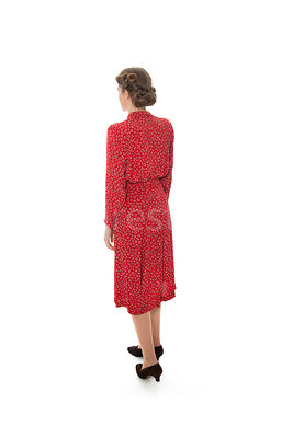 A 1940's woman in a red dress walking away – shot from eye-level.