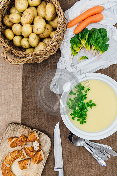 Cream of potato soup topped with chopped green onions in a white soup pot photographed from top view. Sliced Turkish simit on a wooden board, baby potatoes in a basket, carrots and spinach leaves accompany.