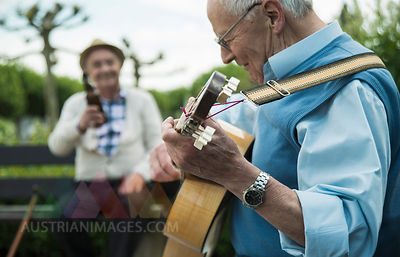 Two old men with guitar in the park