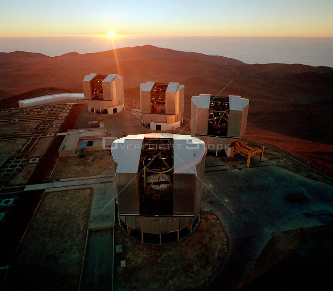 CHILE Mount Paranal -- Dec 1999 -- Aerial view of the Paranal summit, with the Sun setting over the cloud-covered Pacific Ocean.