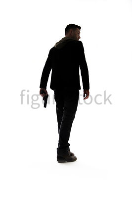A Figurestock image of a man with a gun, in silhouette, walking away – shot from low level.