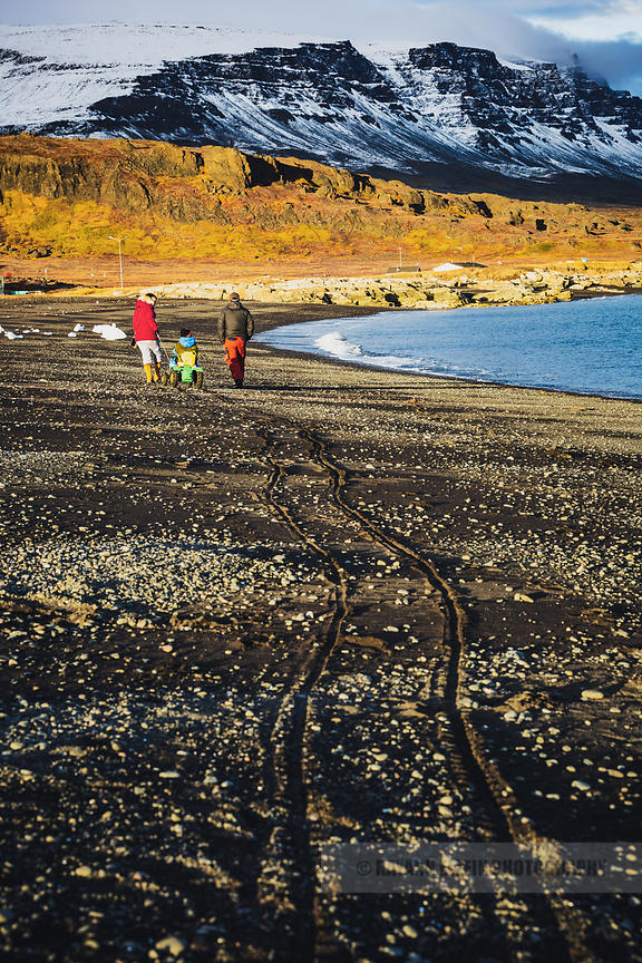A family takes an evening stroll on the black sand beach of Qeqertarsuaq in Greenland