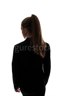 A woman, in semi-silhouette, standing and looking away – shot from above eye level..