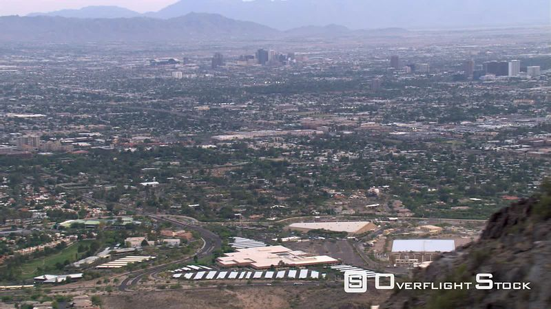 Wide view of distant downtown Phoenix and outlying areas, rocky peak through frame.