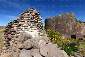 Base of cut stone Inca period chulpa / burial tower and older rough stone chulpa, Sillustani, Peru
