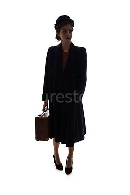 A semi-silhouette of a 1940's woman in a hat and a coat, carrying a suitcase – shot from eye-level.