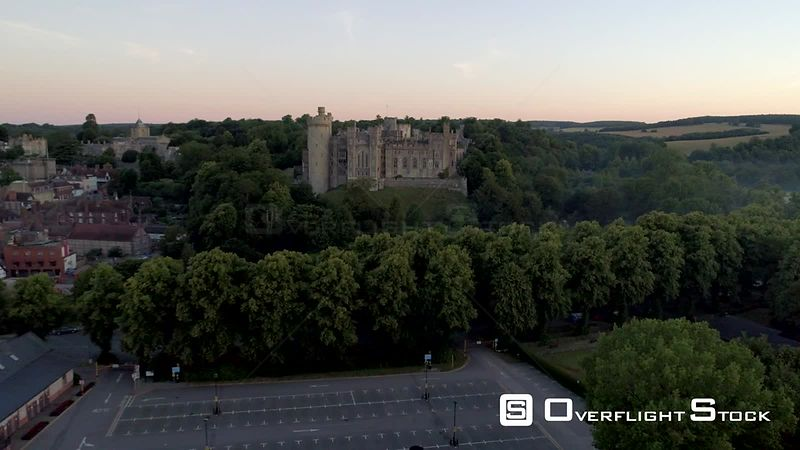 Camera rises from behind trees to reveal Arundel Castle in a misty dawn. West Sussex