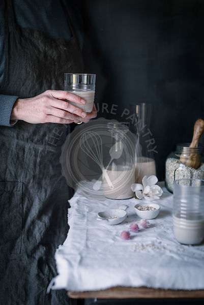 A woman holding a glass of Homemade Oatmeal milk