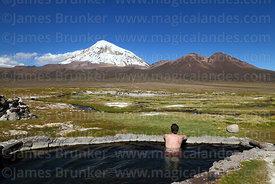 Tourist enjoying view of Sajama volcano from thermal pool at Manasaya hot springs, Sajama National Park, Bolivia