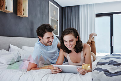 Smiling couple lying on bed shopping online
