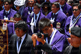 Devotee of Señor de los Milagros filming the central mass for the Virgen de la Candelaria festival using a Canon Rebel T5i digital camera, Puno, Peru