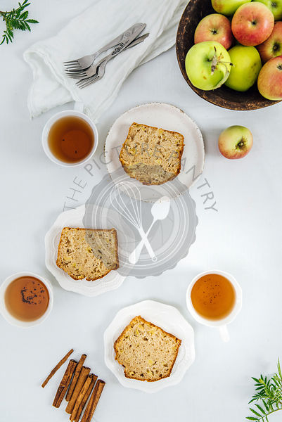 Cinnamon apple bread slices served on three white plates photographed from top view. Three cups of tea and apples in a wooden bowl accompany.