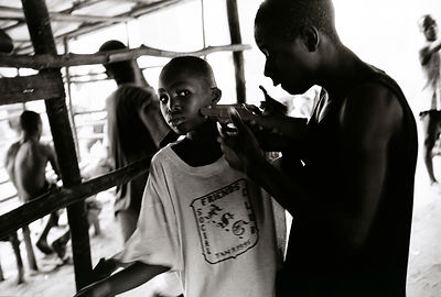 Liberia - Monrovia - A former combatant threatens a young boy with a toy gun