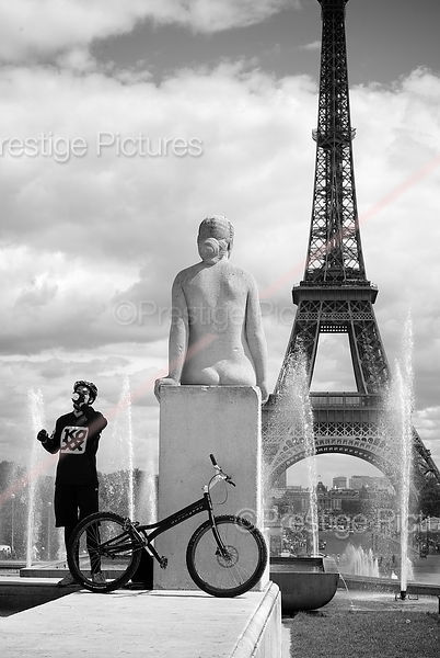 Stunt Cyclist taking a Drink with The Eiffel Tower Behind