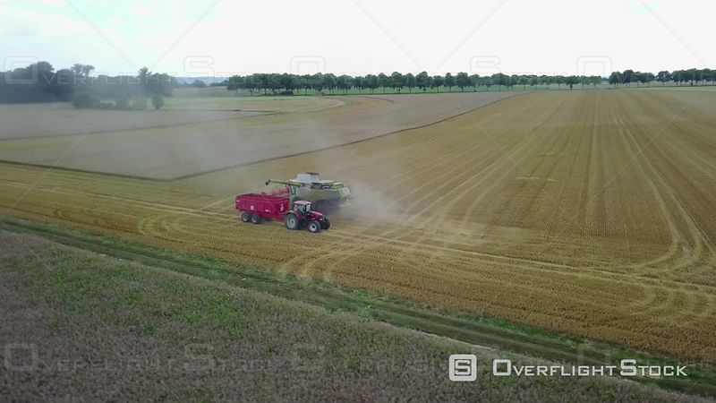 Aerial view of a combine-harvester and a tractor in a wheat field, filmed by drone, Pommeuse, France
