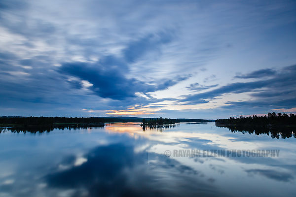 Perfect reflection of the sky on the quiet water of the Paatsjoki River near the Russian border