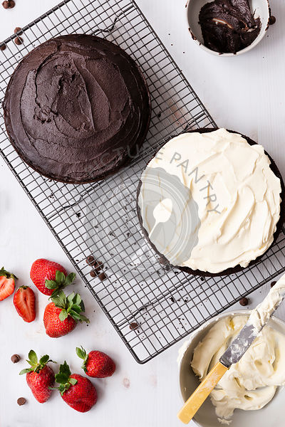 Round chocolate cake on a cake rack covered with chocolate icing and filled with cream.