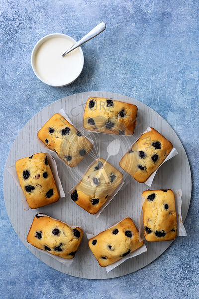 Individual blueberry loaf cakes on a round blue wooden serving board with a bowl of cream.
