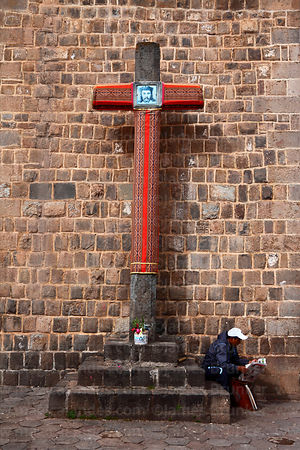 Man reading newspaper beneath cruz velakuy cross next to San Blas church, Cusco, Peru