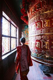 Local woman near prayer wheel, Kathmandu, Nepal