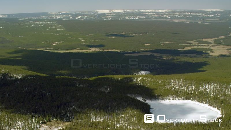 Mary Lake sits ice covered in dense lodgepole forests in Yellowstone National Park