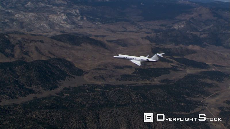 Business jet flying over rugged terrain, air-to-air view