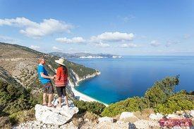 Tourist couple looking down to Myrtos beach, Kefalonia, Greece