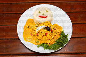 Aji de gallina / shredded chicken in a spicy yellow cheese sauce with rice, Peru