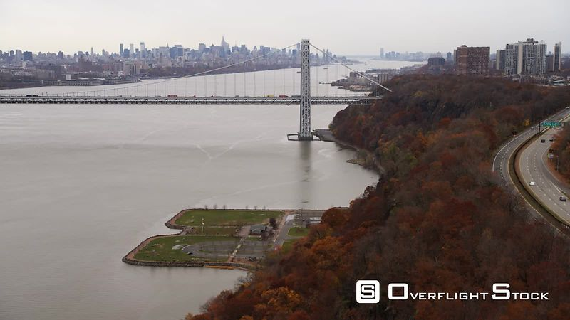 Flying along west shore of Hudson River to George Washington Bridge, New York City skyline in background.