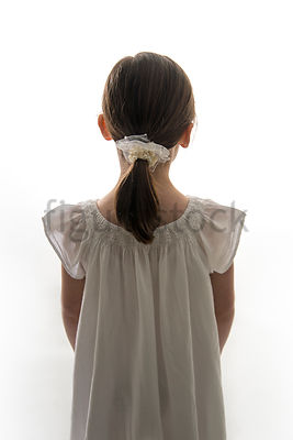 A Figurestock image of a little girl in a dress, from behind – shot from eye level.