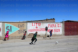 Schoolchildren running past propaganda showing support for Evo Morales and the industrialisation of the Salar de Uyuni's lithium reserves, Colchani, Bolivia