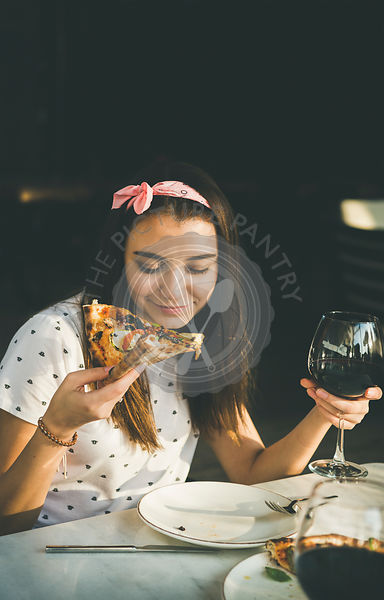 Young caucasian woman eating pizza and drinking wine, copy space