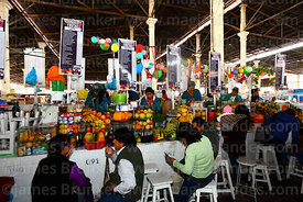 Customers at stalls serving freshly made fruit juice in San Pedro market, Cusco, Peru