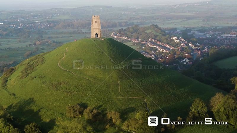 Aerial shot tracking towards St, Michael's Church Tower and Glastonbury Tor at sunrise, Somerset Levels, England, UK, October 2017.