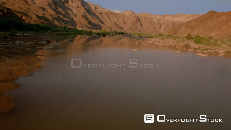 Aerial close up flying up river with mountain range reflected in water and green vegetation and stones sides of river Fish River Canyon Namibia